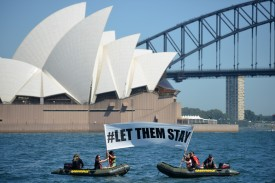 Members of the environmental group Greenpeace hold up a sign calling for Australia to allow refugee children to stay in the country in Sydney on February 14, 2016, after a hospital in Brisbane refused to send an asylum-seeker baby back to detention on Nauru.