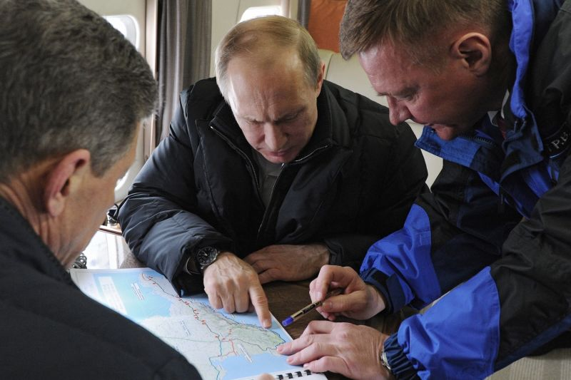 Russian President Vladimir Putin points at a map while inspecting the construction of a bridge across the Kerch Strait, linking Russia and the Crimean peninsula, while aboard a helicopter on March 18, 2016. (Mikhail Klimenty/AFP/Getty Images)