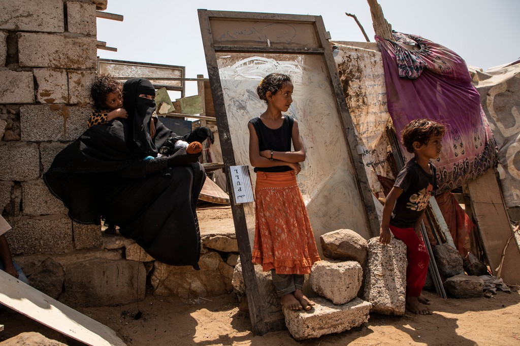 A woman displaced by fighting in Taiz sits outside her temporary home with her family on the outskirts of Aden, Yemen, on Oct. 15. (Will Swanson for Foreign Policy)