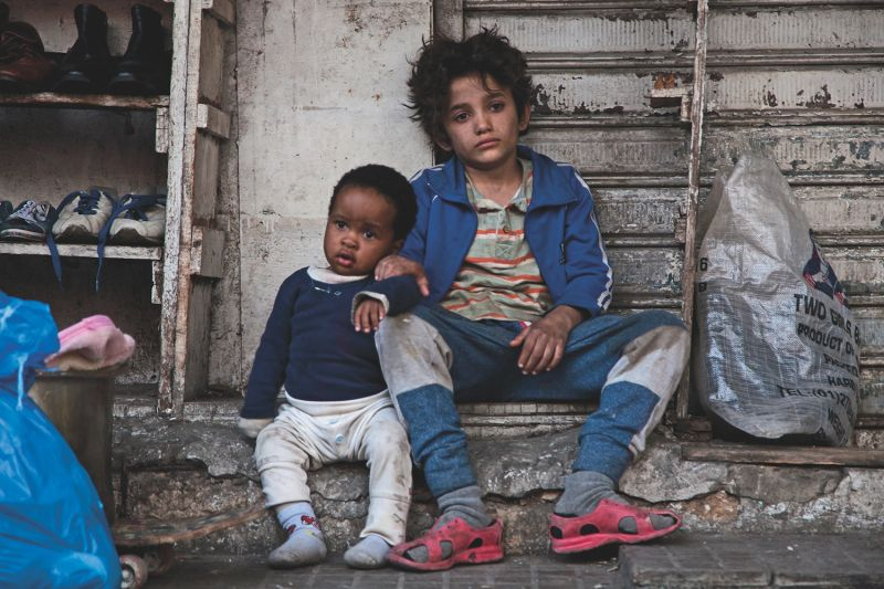 Zain (Zain Al Rafeea), right, cares for Rahil's son, Yonas (Boluwatife Treasure Bankole), after  Rahil is detained in Nadine Labaki's Capernaum. (Fares Sokhon/Sony Pictures Classics)