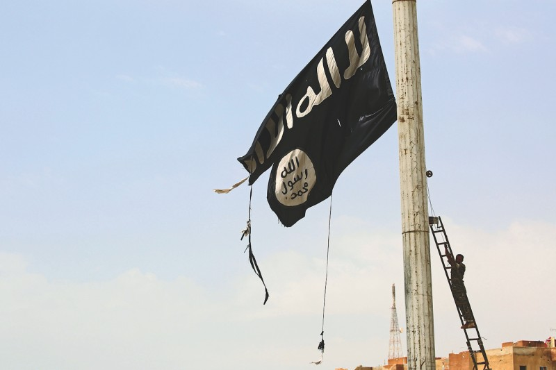 A member of the U.S.-backed Syrian Democratic Forces takes down a tattered Islamic State flag in Tabqa, Syria, in April 2017. (Delil Souleiman/AFP/Getty Images)