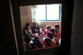 Children gather around a stainless steel can of soy milk at a day care in Tongchon, North Korea, on Dec. 3. (John Lehmann for First Steps)
