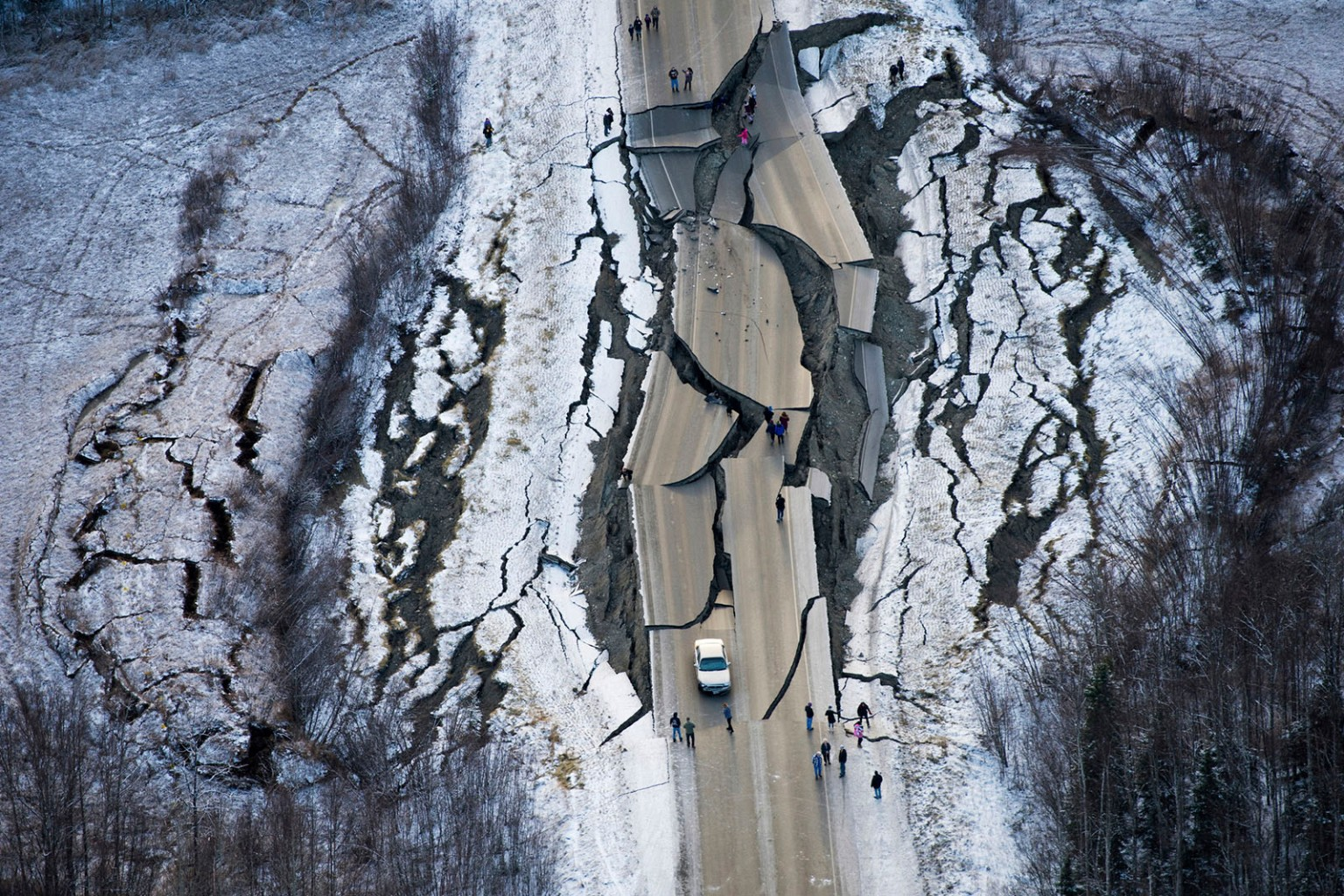 Cracks stop traffic on Vine Road, south of Wasilla, Alaska, after earthquakes on Nov. 30. Back-to-back quakes measuring 7.0 and 5.7 shattered highways and rocked buildings in Anchorage and the surrounding area, sending people running into the streets and briefly triggering a tsunami warning for islands and coastal areas south of the city. Marc Lester/Anchorage Daily News via AP