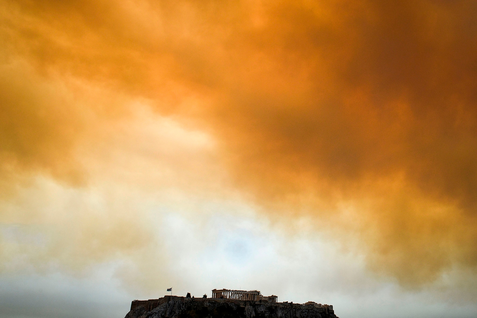 Smoke billows behind the Parthenon on the Acropolis in Athens during a nearby wildfire in Kineta, Greece, on July 23. Wildfires killed at least 91 people in villages surrounding Athens, devouring homes, cars, and forests. VALERIE GACHE/AFP/GETTY IMAGES