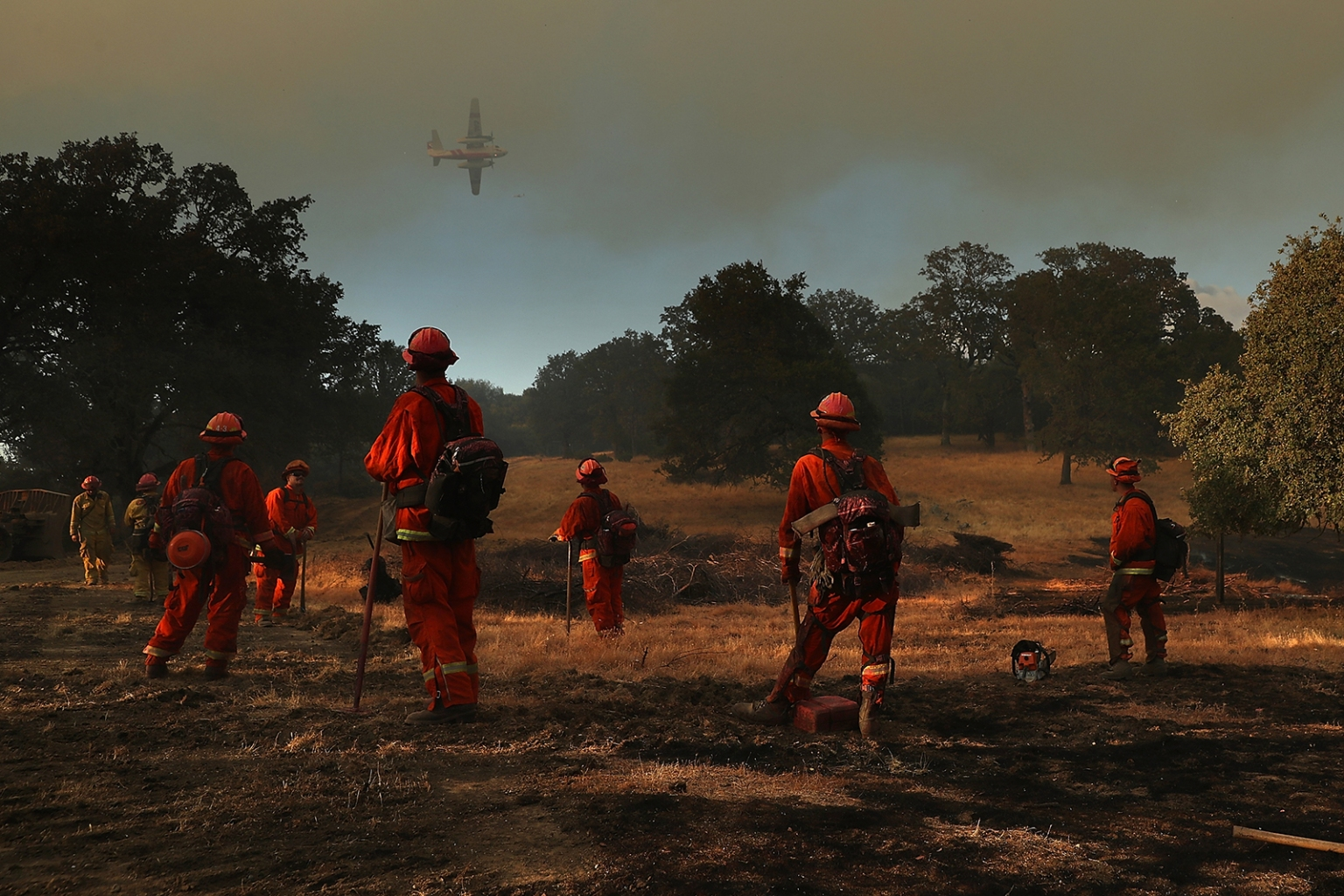 Inmate firefighters watch as an aircraft prepares to drop fire retardant ahead of the River Fire as it burns through a canyon in Lakeport, California, on Aug. 1. Justin Sullivan/Getty Images