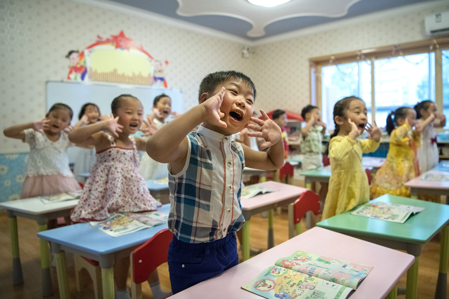 North Korean children gesture and shout at the instruction of a teacher at Gyeongsang Kindergarten in Pyongyang on Aug. 23. CARL COURT/GETTY IMAGES