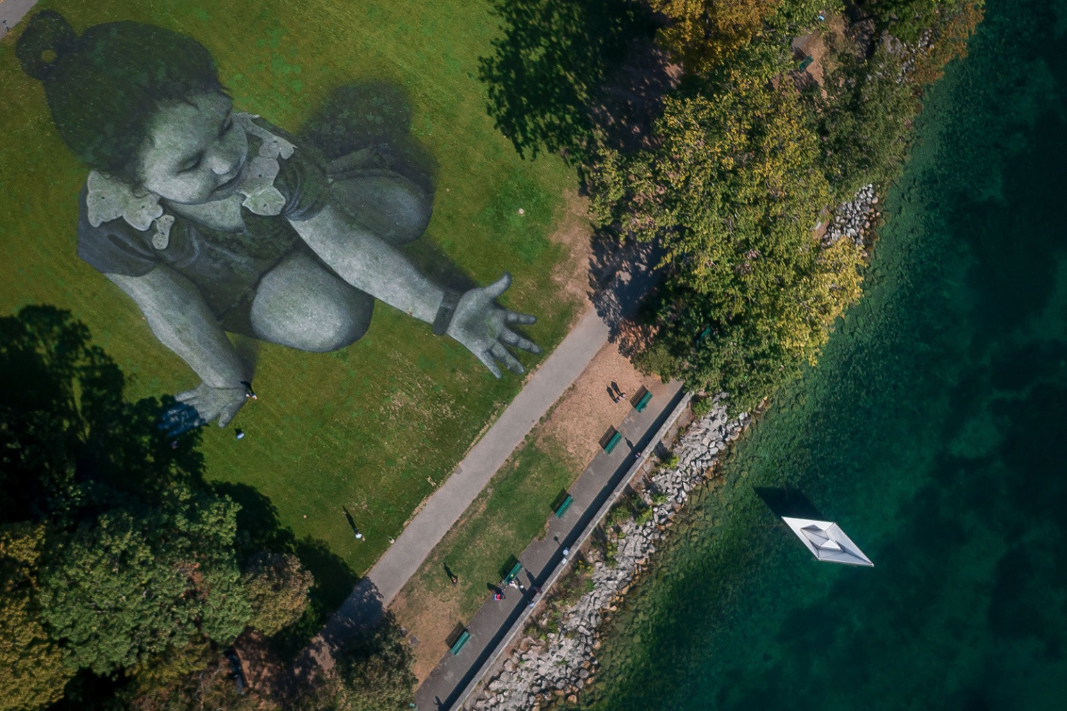The giant land art fresco by French artist Saype in Geneva appears 3-dimensional from above on Sept. 17. The work shows a little girl dropping an origami boat into Lake Geneva and was painted to support the cause of the nongovernmental organization SOS Méditerranée, which specializes in the rescue of migrants at sea. FABRICE COFFRINI/AFP/GETTY IMAGES