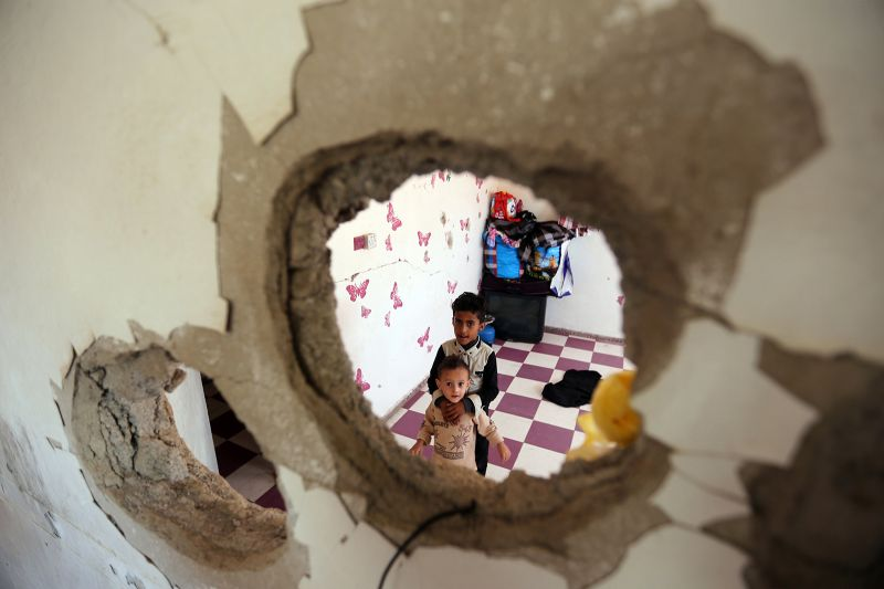 Yemeni children from the Hodeidah province are seen through a hole in a damaged house where they have been living with other displaced families in the southwestern city of Taez on Sept. 30. (Ahmad Al-Basha/AFP/Getty Images)