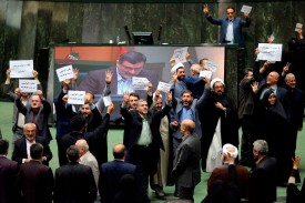Iranian members of parliament display their disagreement over a bill, one of four put forward by the government to meet demands set by the international Financial Action Task Force,  in Tehran on Oct. 7. (Atta Kenare/AFP/Getty Images)
