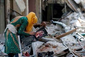 A woman looks for items to salvage amid the wreckage of a street in Yarmouk, in Damascus, Syria, on Oct. 9. (Louai Beshara/AFP/Getty Images)