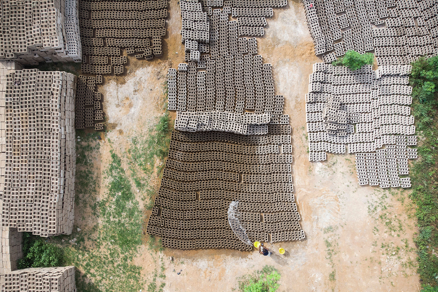 A Malian worker pours water on sun-dried bricks made from river sand at a factory in Bamako on Oct. 9. MICHELE CATTANI/AFP/Getty Images