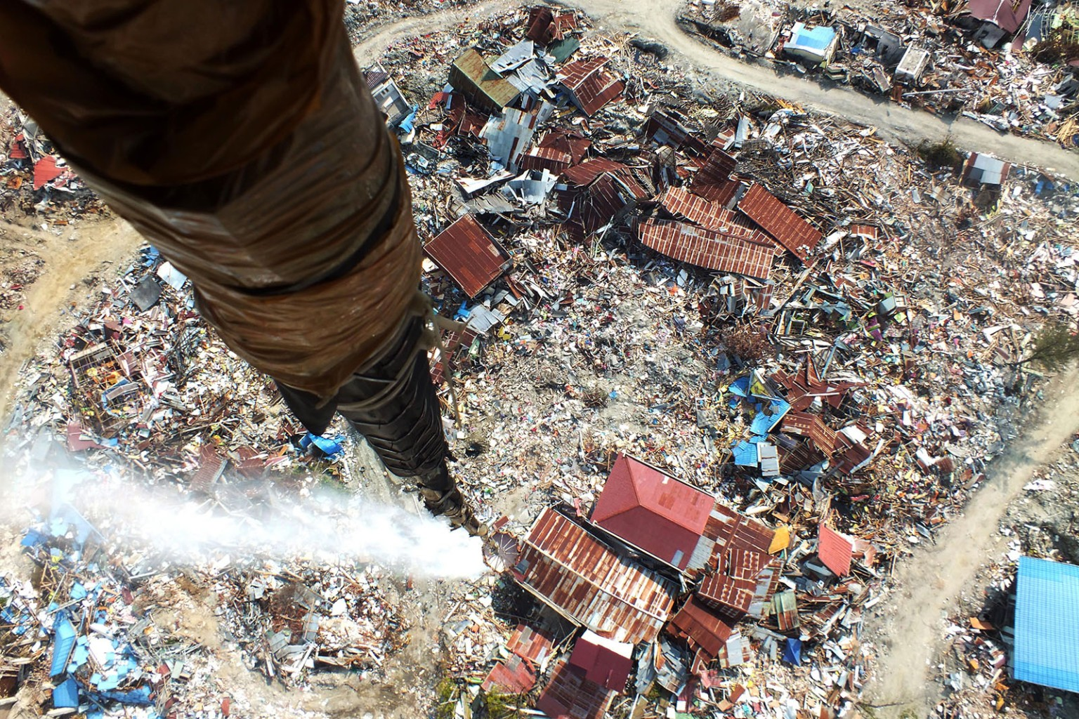 Disinfectant is released over Palu, Indonesia, on Oct. 14 in an attempt to sterilize the area affected by liquefaction in the Sept. 28 earthquake and where thousands are still feared buried. MUHAMMAD RIFKI/AFP/Getty Images