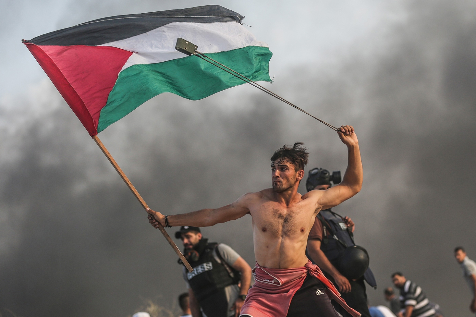 Palestinians throw stones and burn tires in response to Israeli forces' intervention as they gather to support the maritime demonstration to break the Gaza blockade by sea with vessels in Gaza City on Oct. 22. This photo of a shirtless protester went viral after its release, drawing comparisons to the iconic French Revolution painting Liberty Leading the People. MUSTAFA HASSONA/ANADOLU AGENCY/GETTY IMAGES