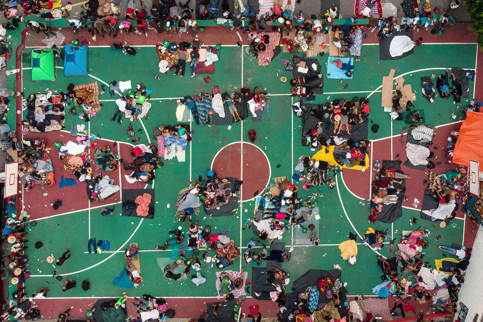 Honduran migrants rest on a basketball court in San Pedro Tapanatepec, southern Mexico, during thier trip toward the United States on Oct. 28. GUILLERMO ARIAS/AFP/Getty Images