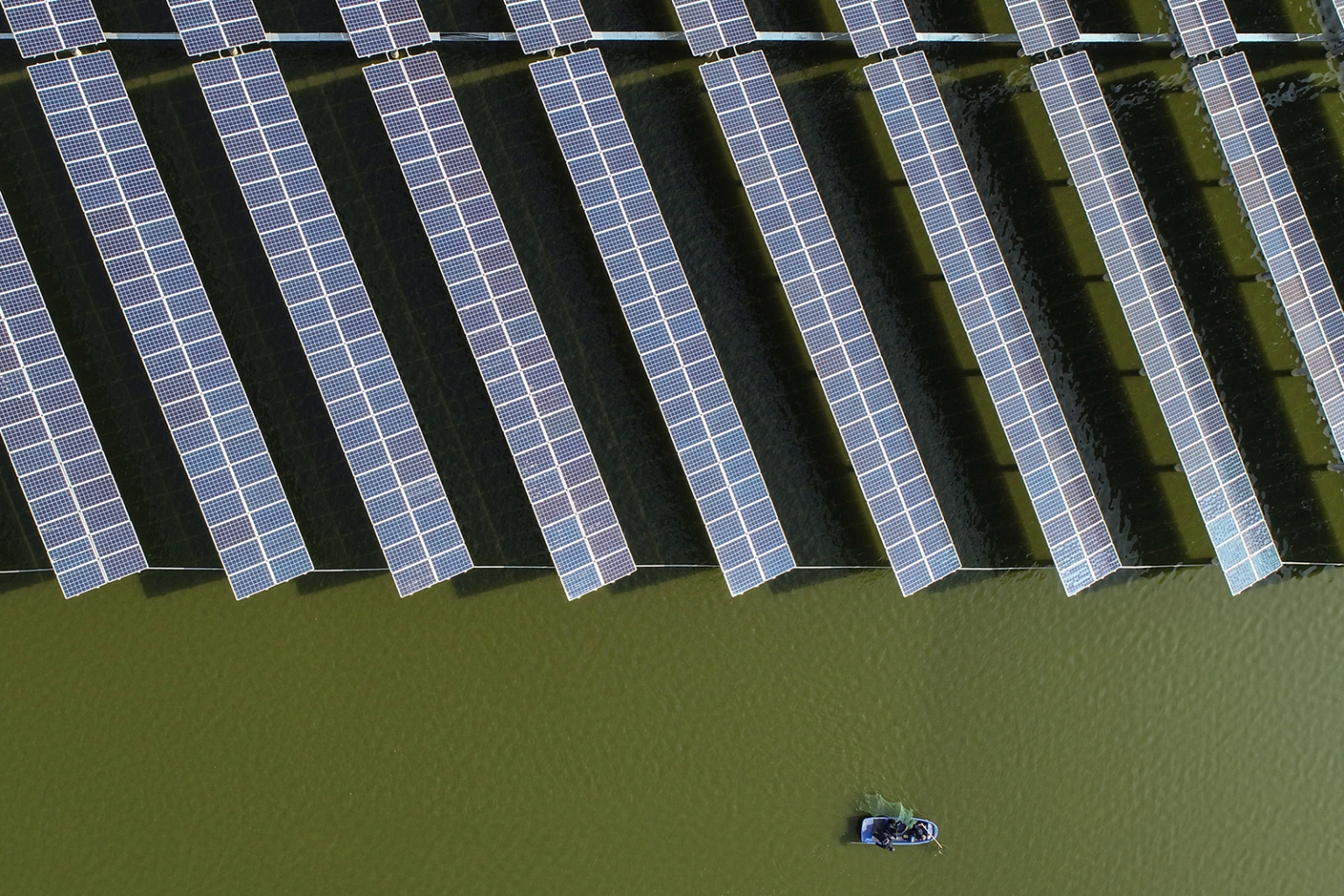 Chinese fishermen float next to a photovoltaic power station built atop fish ponds in Yangzhou in China's eastern Jiangsu province on Nov. 14. STR/AFP/Getty Images