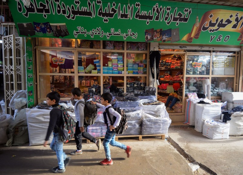 Iraqi boys walk past a shop in a local market in the northern city of Mosul on Nov. 21. ( Zaid al-Obeidi/AFP/Getty Images)