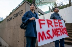 VANCOUVER, BC - DECEMBER 10: Supporters Ada Yu and Wade Meng (no relation) stand with a sign outside BC Supreme Court before the bail hearing for Huawei Technologies CFO Meng Wanzhou on December 10, 2018 in Vancouver, Canada. (Photo by Rich Lam/Getty Images)