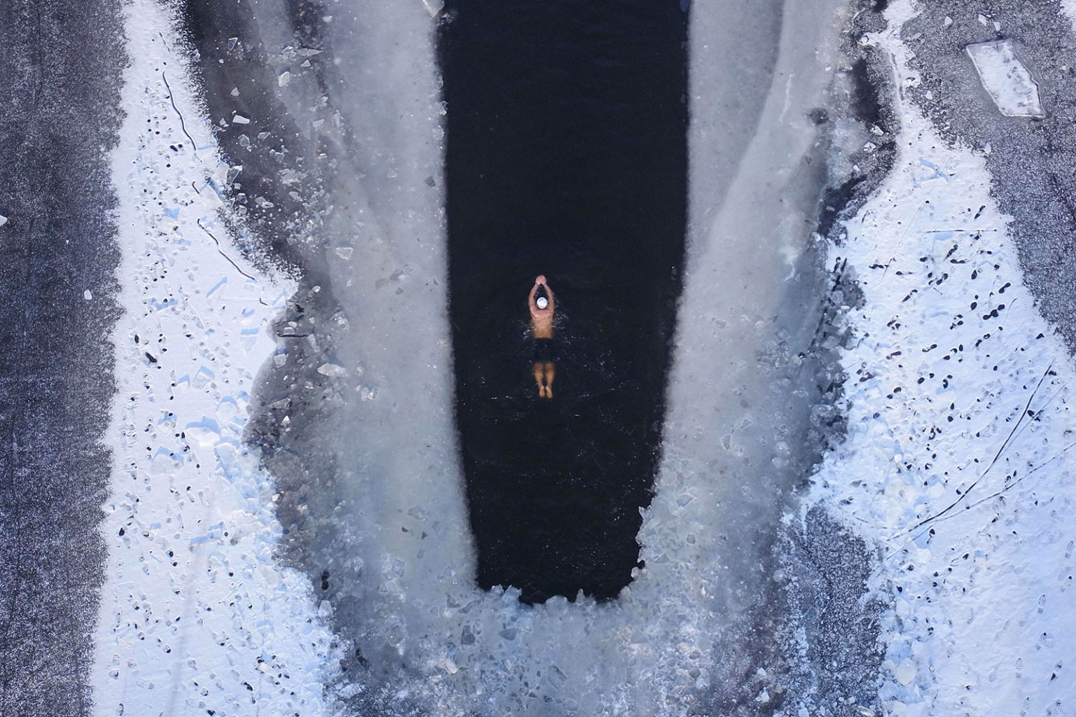 A man swims in a partly frozen lake in Shenyang in China's northeastern Liaoning province on Dec. 10. STR/AFP/Getty Images