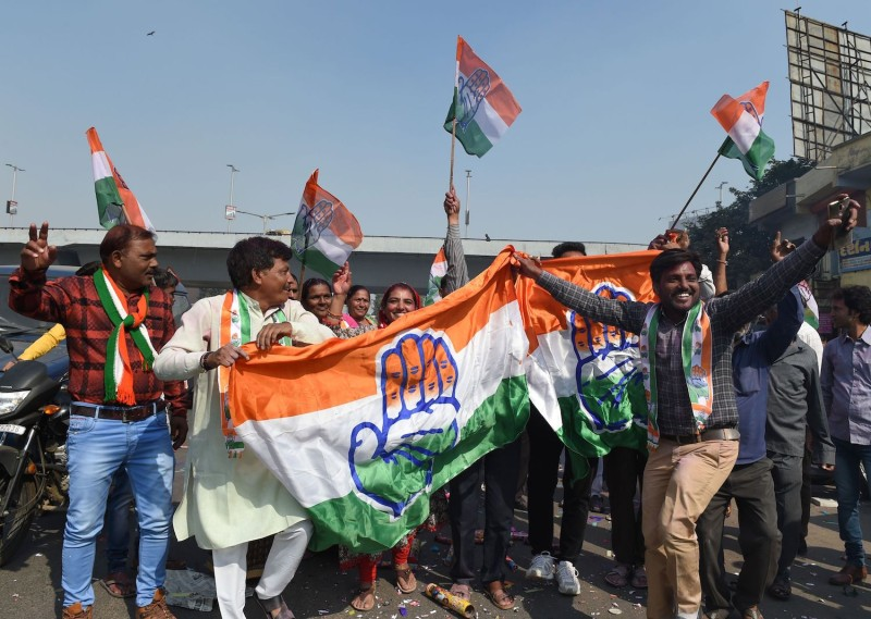 Indian Congress party supporters hold a party flag as they celebrate in Ahmedabad on December 11, 2018. (Sam Panthaky/AFP/Getty Images)