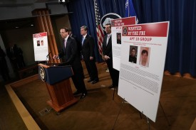 U.S. Deputy Attorney General Rod Rosenstein speaks as FBI Director Chris Wray and Assistant Attorney General for National Security John Demers listen during a news conference to announce a China-related national security law enforcement action at the Justice Department in Washington on Dec. 20. (Alex Wong/Getty Images)