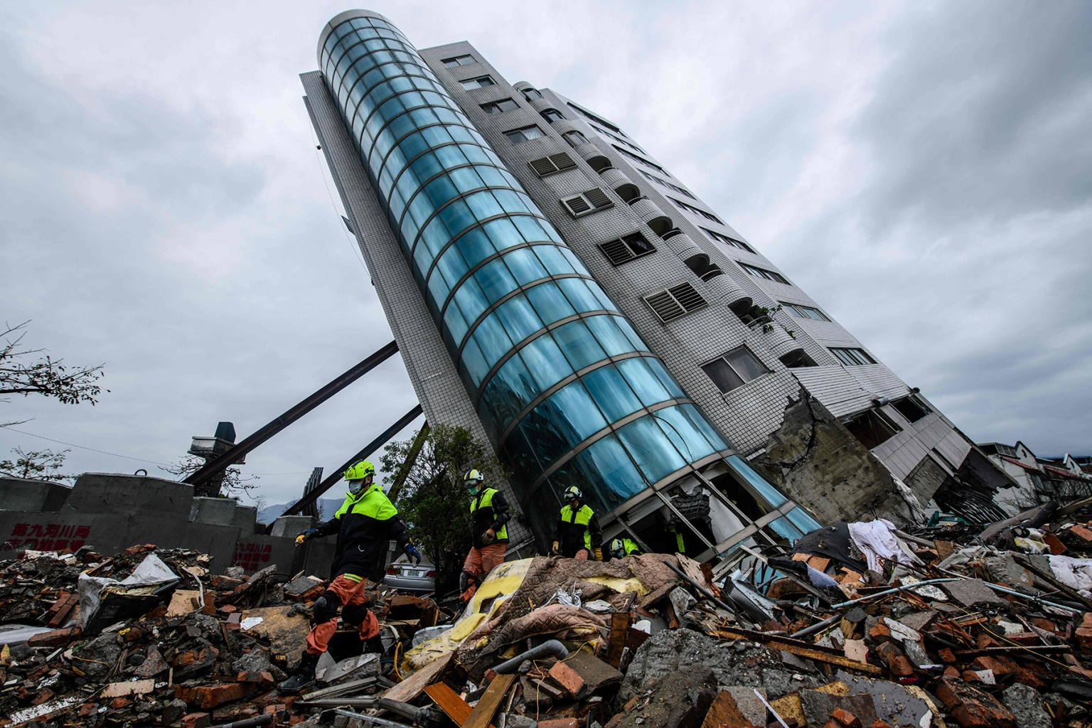 Rescue workers walk out from the Yun Tsui building, which leans at a precarious angle, in the Taiwanese city of Hualien on Feb. 8 after the city was hit by a 6.4-magnitude quake on Feb. 6. ANTHONY WALLACE/AFP/Getty Images