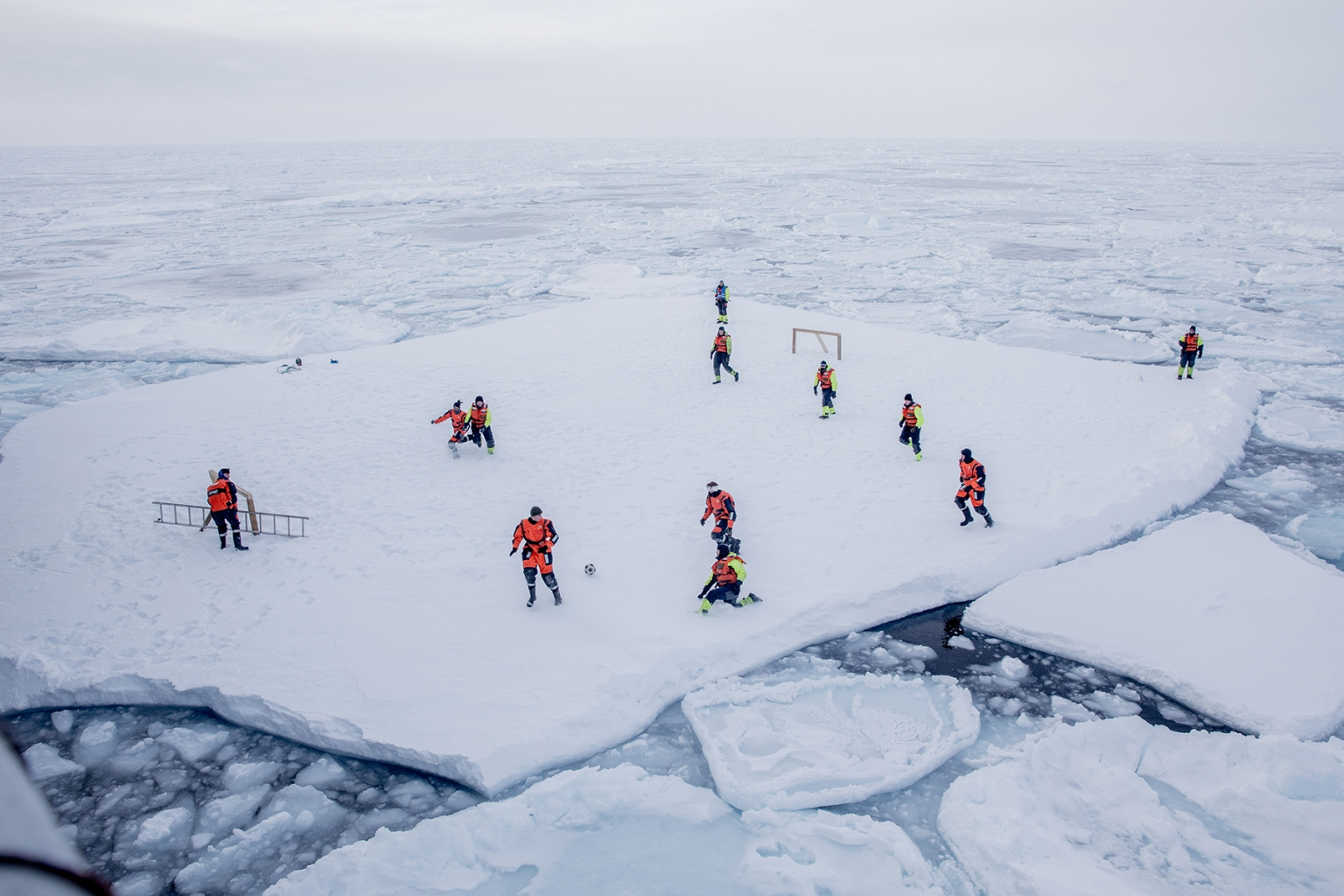 The crew of patrol vessel KV Svalbard and scientists from the Norwegian Institute of Marine Research play soccer on ice offshore in the sea around Greenland while two armed guards look out for polar bears on March 22 . MARIUS Vågenes VILLANGER/AFP/Getty Images