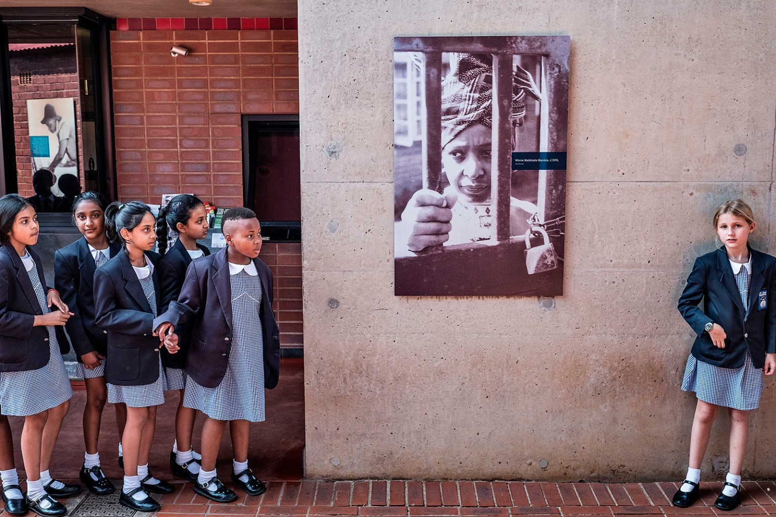 "South African schoolchildren pause next to a portrait of South African anti-apartheid campaigner Winnie Madikizela-Mandela at her house in Soweto, South Africa, on April 3. ""The Mother of the Nation"" and Nelson Mandela's former wife died April 2 at age 81. MARCO LONGARI/AFP/GETTY IMAGES"