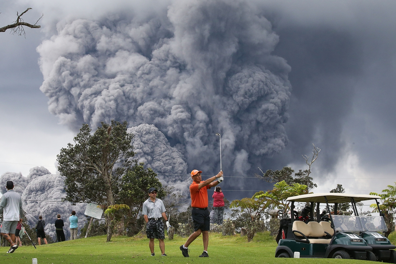 People play golf as an ash plume rises in the distance from the Kilauea volcano in Hawaii Volcanoes National Park on Hawaii's Big Island on May 15. Another violent eruption on May 17 sent ash 30,000 feet into the sky, with the U.S. Geological Survey warning that ash could fall as far as Hilo, 30 miles away. MARIO TAMA/GETTY IMAGES