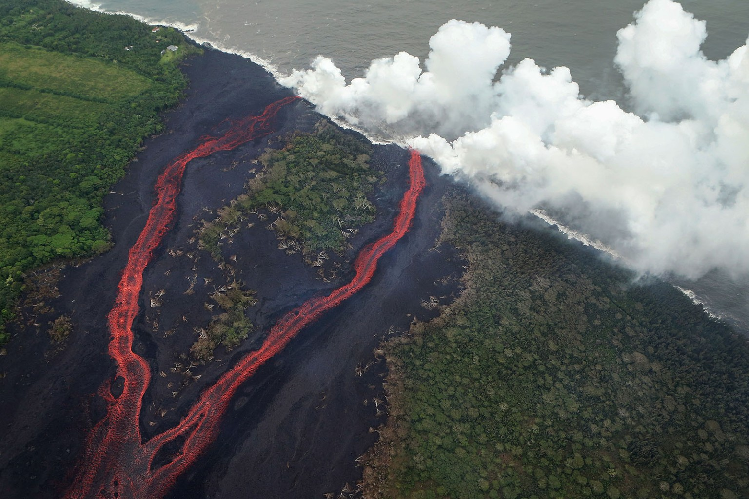 Steam plumes rise as lava hits the Pacific Ocean after flowing from a Kilauea volcano fissure on Hawaii's Big Island near Pahoa on May 21. MARIO TAMA/GETTY IMAGES
