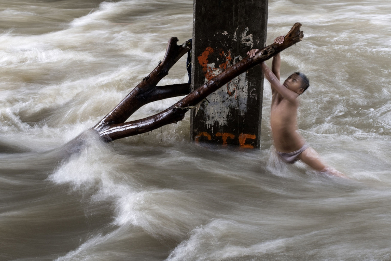 A boy holds a partially submerged branch as he plays under a bridge in a swollen river after heavy rains in Manila on June 11. NOEL CELIS/AFP/Getty Images