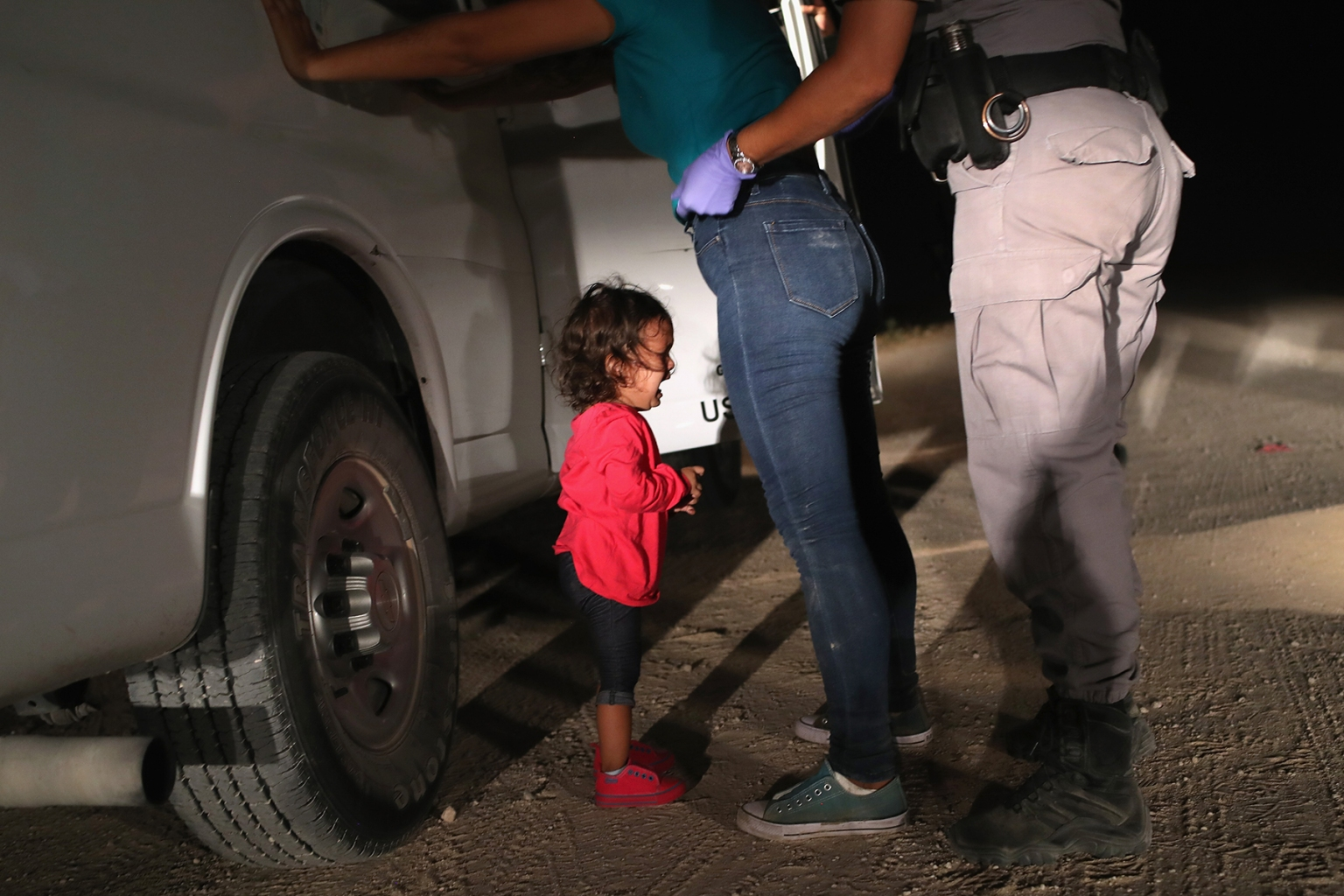 A 2-year-old Honduran asylum seeker cries as her mother is searched and detained near the U.S.-Mexico border in McAllen, Texas, on June 12. John Moore/Getty Images