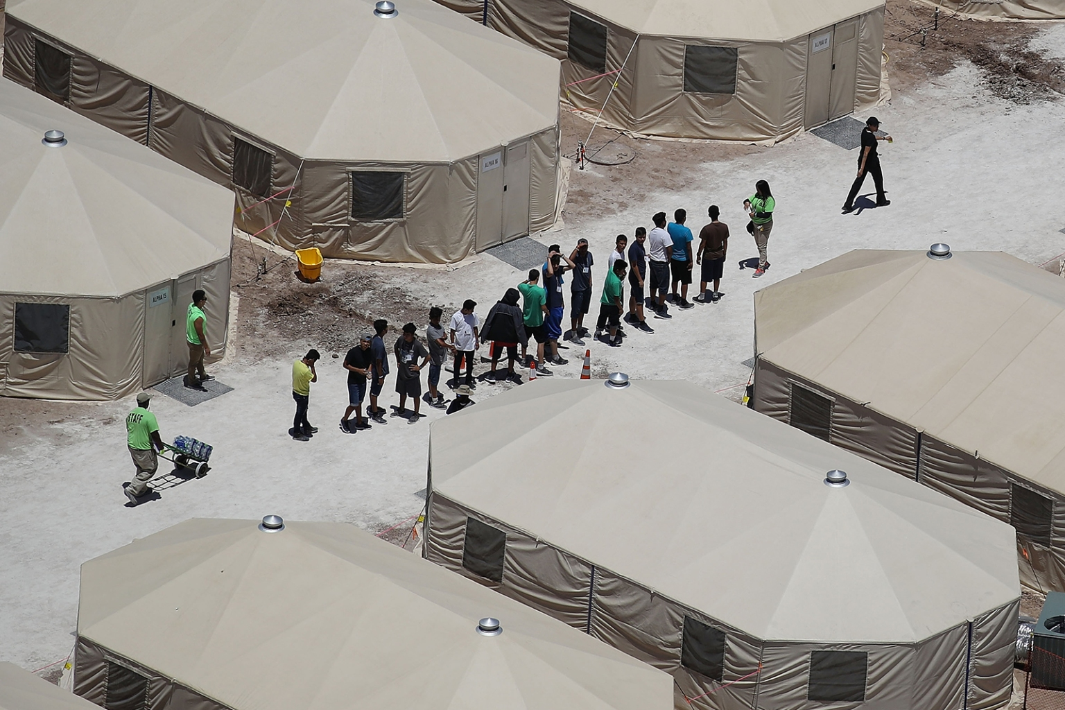 "Children and workers are seen at a tent encampment recently built near the Tornillo Port of Entry in Tornillo, Texas, on June 19. The Trump administration is using the facility to house some of the immigrant children separated from their parents after they were caught entering the United States under the president's ""zero tolerance"" policy. JOE RAEDLE/GETTY IMAGES"