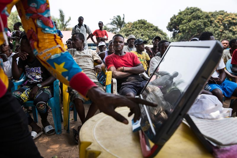 Michée Yolona Selenga of the Independent National Electoral Commission tests an electronic voting machine during a voter information session in Mbenzale near Kinshasa, Democratic Republic of the Congo, on Aug. 21. (Holly Pickett for Foreign Policy)