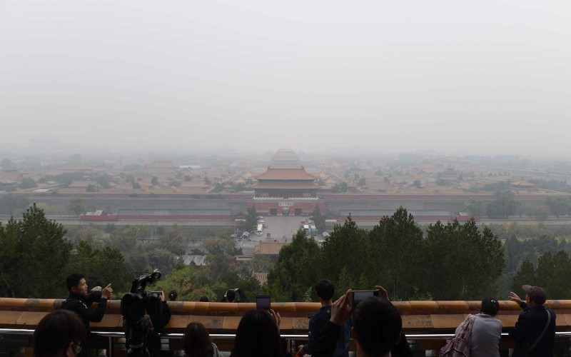 People (front) take photos of the Forbidden City (C) on a polluted day in Beijing on October 15, 2018. (NICOLAS ASFOURI/AFP/Getty Images)