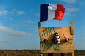 A man poses on a pillory with a French flag during a demonstration against rising fuel prices on Nov. 17, 2018 in Dole, France. (Sebastien Bozon/AFP/Getty Images)
