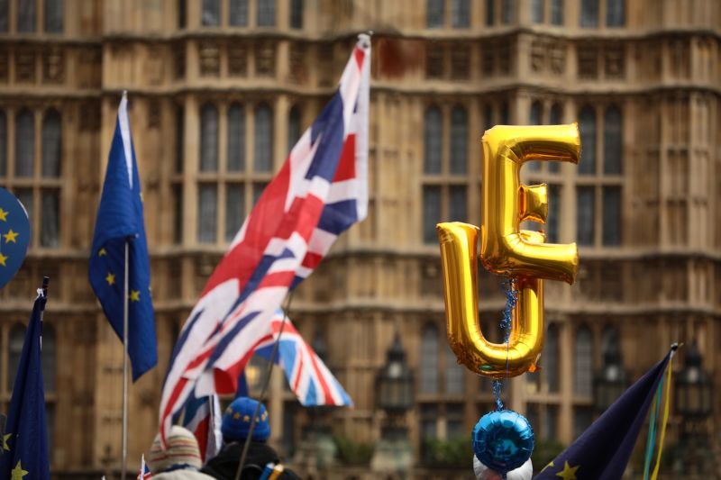 Balloons spelling EU fly beside Union Jack and European Union flags outside the Houses of Parliament in London on Dec. 10, 2018. (Dan Kitwood/Getty Images)