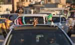 Iraqi men flash the victory gesture from inside a car during the Hashed Shaabi (Popular Mobilisation) paramilitary forces' celebrations marking the first anniversary of victory over the Islamic State (IS) group on December 10, 2018. (Mohammed Sawaf/AFP/Getty Images)