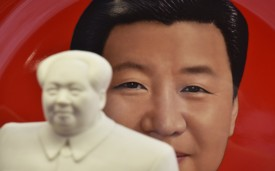A decorative plate featuring an image of Chinese President Xi Jinping is seen behind a statue of late communist leader Mao Zedong at a souvenir store next to Tiananmen Square in Beijing on February 27, 2018.(GREG BAKER/AFP/Getty Images)