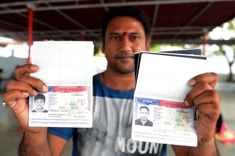Angirekula Sreekanth poses for a photograph with a copy of his U.S. visa and those of his relatives at the Chilkur Balaji Temple in Rangareddy district, near Hyderabad, on April 29, 2017.