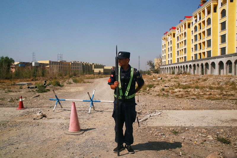 """A Chinese police officer takes his position by the road near what is officially called a """"vocational education and training program"""" in Yining, in Xinjiang, China, on Sept. 4, 2018. (Thomas Peter/Reuters)"""