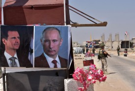 Members of Russian and Syrian forces stand guard near posters of Syrian President Bashar al-Assad and his Russian counterpart, Vladimir Putin, at the Abu Duhur crossing on the eastern edge of Idlib province on Aug. 20, 2018. (George Ourfalian/AFP/Getty Images)