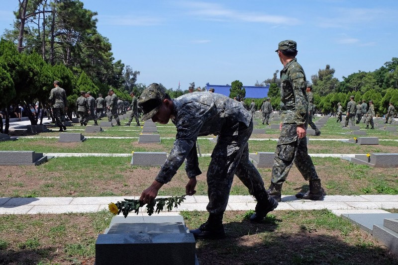 A soldier puts a flower on a grave in a cemetery for soldiers during the 60th anniversary of the '823 bombardment' in Kinmen, Taiwan on August 23, 2018.   (SAM YEH/AFP/Getty Images)