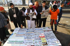 """In Dhaka, people read newspapers carrying headlines outlining the general election results on Dec. 31, 2018. Bangladeshi Prime Minister Sheikh Hasina secured a fourth term with a landslide victory in a vote the opposition slammed as """"farcical"""" over claims of vote-rigging, and clashes between rival supporters that killed at least 17 people. (Indranil Mukherjee / AFP/Getty Images)"""