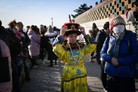 A boy wearing the costume of a Qing emperor prepares to pose for photographs at a park near the Forbidden City in Beijing on Jan. 1. (Wang Zhao/AFP/Getty Images)