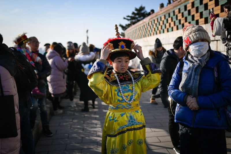 3b6bb3170 A boy wearing the costume of a Qing emperor prepares to pose for  photographs at a
