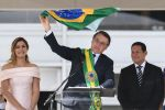 President Jair Bolsonaro waves a Brazilian flag while addressing supporters during his inauguration ceremony in Brasilia on Jan. 1, 2019. (Evaristo Sa/AFP/Getty Images)