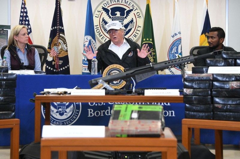 U.S. President Donald Trump, center, with Homeland Security Secretary Kirstjen Nielsen, left, and Reggie Singh, the brother of a police officer who was allegedly killed by a man in the United States illegally, speaks during his visit to U.S. Border Patrol McAllen Station in McAllen, Texas, on Jan. 10. (Jim Watson/AFP/Getty Images)