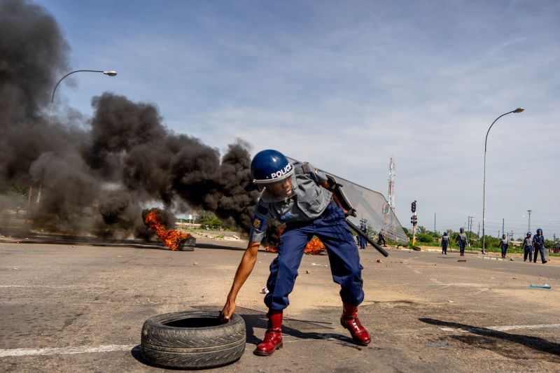 A police officer removes tires set by protesters during a demonstration in Bulawayo, Zimbabwe, on Jan. 14. (Zinyange Auntony/AFP/Getty Images)