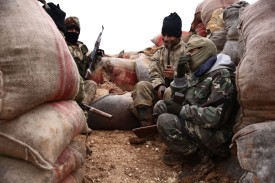 Turkish-backed Syrian opposition fighters gather behind a sandbagged barricade northwest of Manbij in northern Syria on Jan. 15. (Nazeer al-Khatib/ AFP/Getty Images)