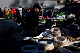 A vendor waits for customers at a Beijing market on Jan. 16. (Fred Dufour/AFP/Getty Images)